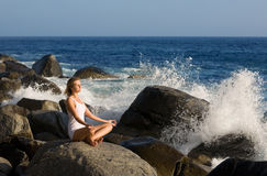 Beautiful girl in lotus position on the stone. Stock Image