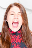 Beautiful girl loudly shout closed eyes in studio Royalty Free Stock Photo