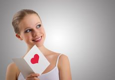 Beautiful girl with a love postcard valentines. On a gray background royalty free stock image