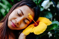 Beautiful girl loving hibiscus flower. Yellow hibiscus flower, spa concept Royalty Free Stock Images