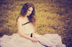 Beautiful girl with luxuriant hair in a long white dress with ba stock photo
