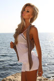 Beautiful girl with luxurious blond hair posing on summer beach Royalty Free Stock Image