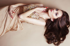 Beautiful girl with luxurious dark hair in sequin dress posing at studio royalty free stock images