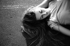 Beautiful girl lying on the asphalt. Black and white Royalty Free Stock Photo