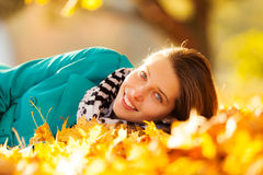 Beautiful girl lying in autumn leaves Stock Photography