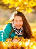 Beautiful girl lying in autumn leaves Stock Photos