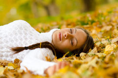 Beautiful girl lying on autumn leaves Royalty Free Stock Photo