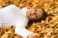 Beautiful girl lying on the autumn leaves Royalty Free Stock Photos