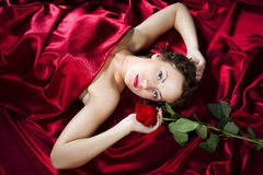Beautiful girl is lying on back on satin cloth and keeping a ros Royalty Free Stock Images