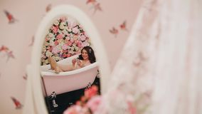 Beautiful girl lying in the bath with phone in hand. A smile on his face. Funny footage. stock video footage
