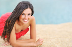 Beautiful girl lying on a beach and smiling Stock Photo