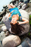 Beautiful girl lying on beach stones Royalty Free Stock Image