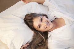 Beautiful girl lying in bed. A beautiful girl lying in her bed Stock Image