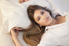 Beautiful girl lying in bed. A beautiful girl lying in her bed Royalty Free Stock Image