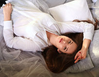Beautiful girl lying in bed and looking up thoughtfully Stock Photography