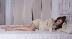 Beautiful girl lying on the bed. In a man's shirt Stock Images