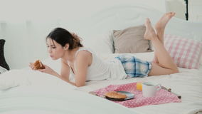 Beautiful girl lying on the bed in morning and chatting, using laptop for that. Young woman eating croissant and typing. Royalty Free Stock Photos