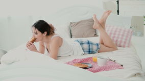 Beautiful girl lying on the bed in morning and chatting, using laptop for that. Young woman eating croissant and typing. Royalty Free Stock Images
