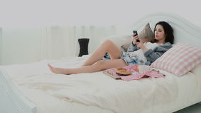 Beautiful girl lying on the bed in morning and using smartphone. Young woman typing, browsing the Internet and yawning. Royalty Free Stock Images