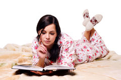 Beautiful girl lying on the bed reading a book Royalty Free Stock Photography