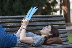 Beautiful girl lying on bench and read blue book, outdoor. Royalty Free Stock Image
