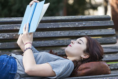 Beautiful girl lying on bench reading blue book, outdoor. Royalty Free Stock Photography