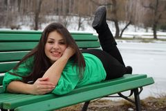 Beautiful girl lying on a bench and smiling Stock Photo