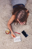Beautiful girl lying on the carpet at home and writing in a notebook next to her cup of tea with lemon stand, top view Stock Photography