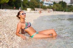 Beautiful girl lying on the coast and taking sunbath. Royalty Free Stock Photo