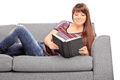 Beautiful girl lying on a couch and reading book Stock Photo