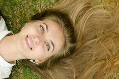 Beautiful girl lying down of grass Stock Image