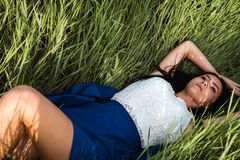 Beautiful girl lying down at grass stock images