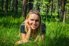 Beautiful girl lying down on grass. Beautiful smiling girl lying down on grass royalty free stock image
