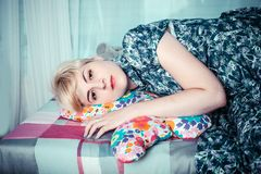 Beautiful girl lying down and hugging a cushion Royalty Free Stock Photography