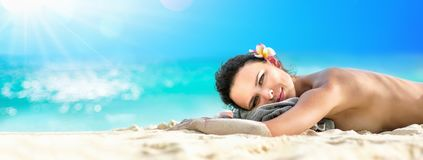 Beautiful Girl Lying Down Under The Sun Tanning In a Tropical Beach stock photo