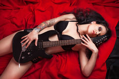 Beautiful girl lying with electro guitar on the be Royalty Free Stock Photography