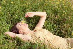 Beautiful girl lying on field of green grass. And holding flowers in her hand Stock Photography