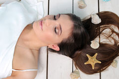 Beautiful girl lying on the floor with seashells in her hair. Portrait. Studio. Stock Photos