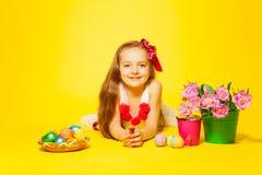 Beautiful girl lying on floor with tulips, eggs Stock Images