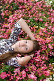 Beautiful girl lying among flowers. In park Royalty Free Stock Photography