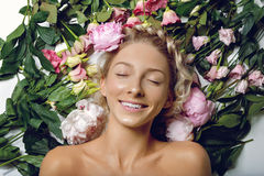 Beautiful girl lying in flowers. Beautiful blond young woman with glowing skin, natural makeup and braided hairstyle lying in blooming flowers. Beauty shot. Copy Royalty Free Stock Image