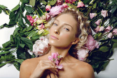 Beautiful girl lying in flowers Stock Photos