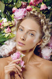 Beautiful girl lying in flowers. Beautiful blond young woman with glowing skin, natural makeup and braided hairstyle lying in blooming flowers. Beauty shot. Copy Stock Photo