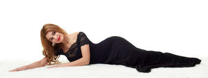 Beautiful girl lying on fur, dressed in black gown. Stock Photo