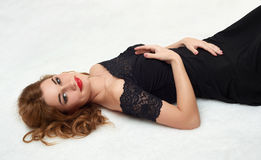 Beautiful girl lying on fur, dressed in black gown. Stock Photography