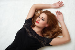 Beautiful girl lying on fur, dressed in black gown. Stock Photos