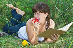Beautiful girl lying on the grass. Portrait of a young beautiful girl, lying on the grass with a book and vegetables Stock Image