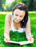 Beautiful girl lying on a grass with book Stock Photography