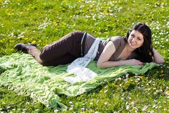 Beautiful girl lying on the grass with flowers Stock Image