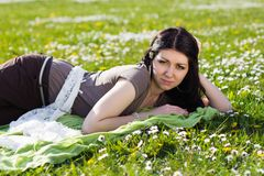 Beautiful girl lying on the grass with flowers Royalty Free Stock Photography